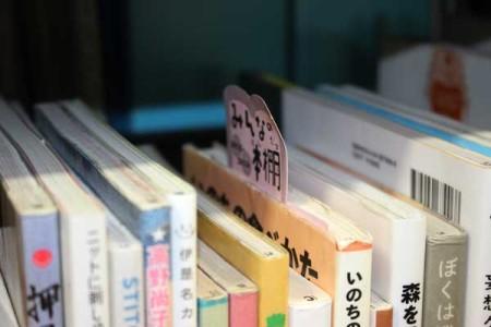書棚に目立つピンクのカード(東久留米市立中央図書館の公開書架)